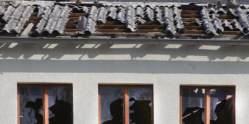 Gebäude mit zerbrochenen Fensterscheiben und teilweise abgedecktem Dach.