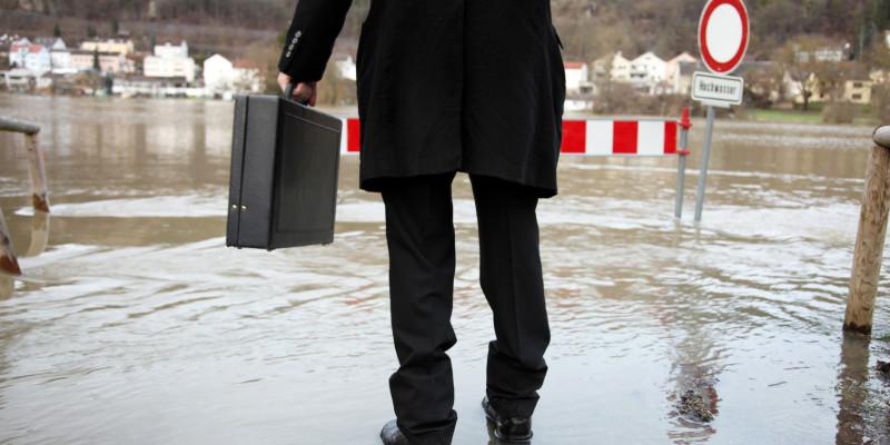 Rückenaufnahme eines Mannes im schwarzen Anzug mit Aktentasche, der auf überfluteter Fläche steht.