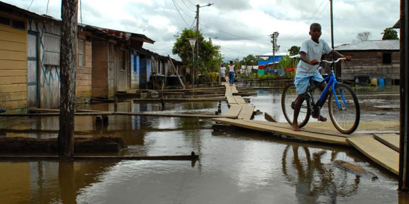 Überschwemmtes Wohngebiet in Entwicklungsland, schwarzes Kind mit Fahrrad auf einem provisorisch angelegten Steg.
