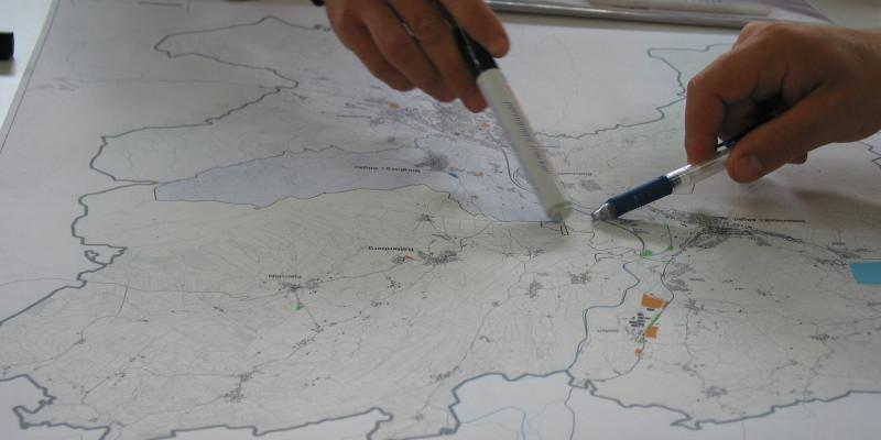 Nahaufnahme von zwei Händen unterschiedlicher Personen, die auf einem Plan mit Stiften auf einen gemeinsamen Ort zeigen.