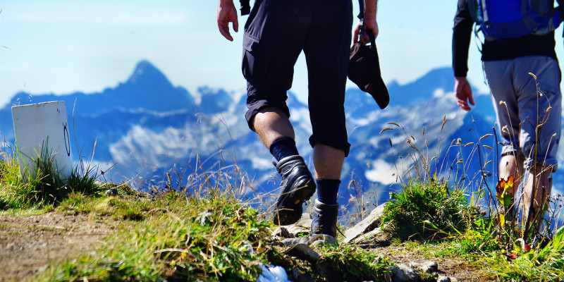 Beine eines Wanderers vor Hochgebirgskulisse.