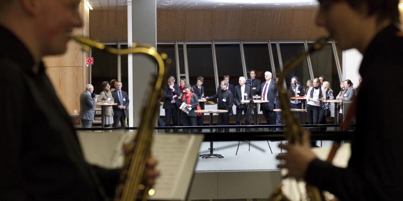 Zwei Saxophon-Spieler im Vordergrund, im Hintergrund der Empfang der Preisträger