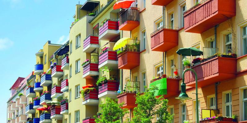 Blockrandbebauung: Mehrere Mehrfamilienhäuser, Neu- und Altbauten mit bepflanzten Balkonen,  Dachausbauten