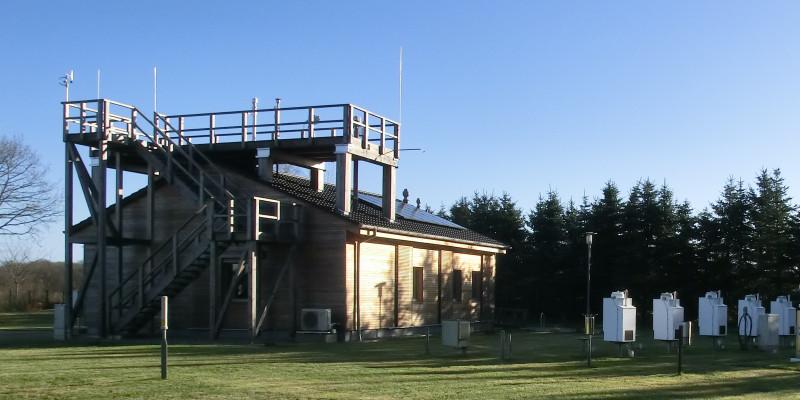 Auf dem Foto sieht man links die UBA-Luftmessstation Zingst und rechts Probenahme-Einrichtungen für die Bestimmung der nassen Deposition von Schwermetallen (Depositionssammler).