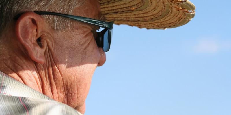Älterer Mann mit Strohhut und Sonnenbrille