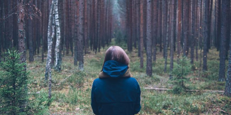 Frau steht mit Rücken zugewandt im Wald.