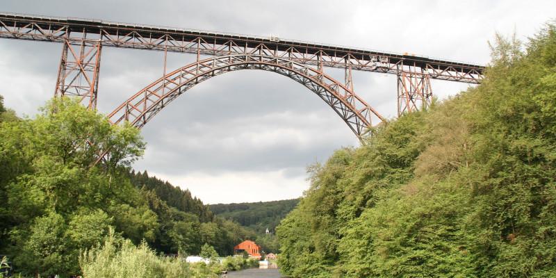 Eine Eisenbahnbrücke spannt sich über einem Fluss, in dem Menschen fröhlich baden - trotz dunkler Wolken am Horizont.