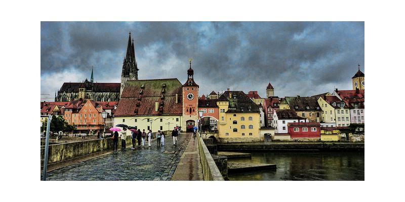 Blick auf Regensburg im Regen von einer Brücke.