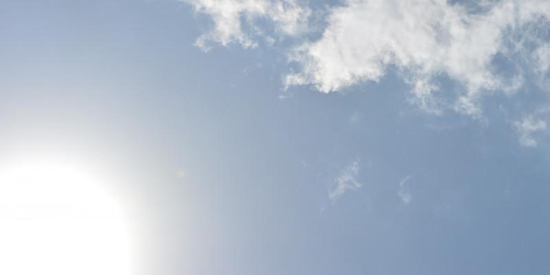 strahlende Sonne an blauem Himmel mit eine paar Wölkchen