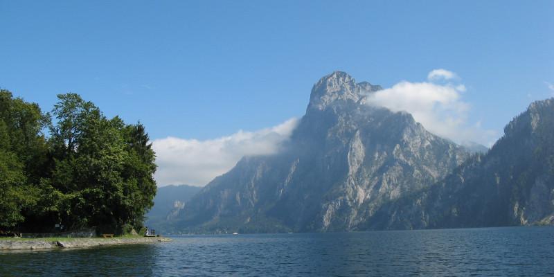 Glatter Seeit Bergen im Hintergrund während rechts noch zwei Bäume zu sehen sind
