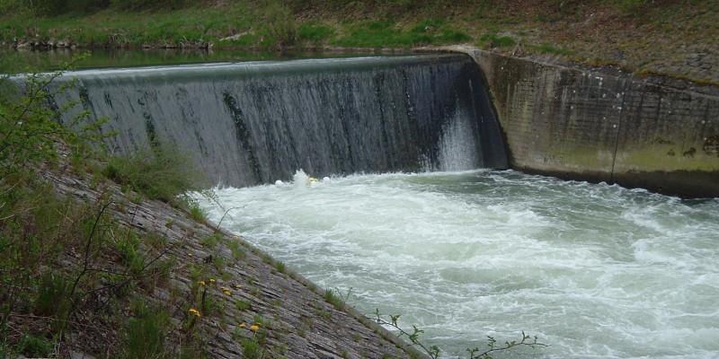 Querbauwerk in einem Fluss - Wasser fließt senkrecht eine Wand herunter