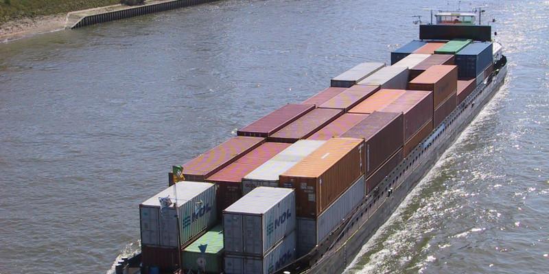 Ein großes Containerschiff fährt bei Sonnenschein auf dem Rhein