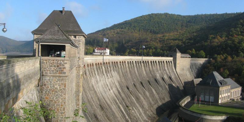 Blick von der Seite auf eine große Talsperre, die aussieht wie eine riesige Mauer
