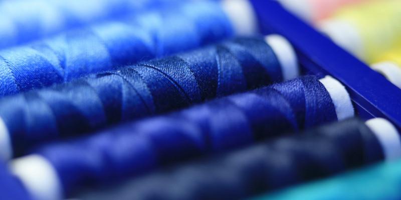 Eine Nahaufnahme von blauem Nähgarn auf Rollen