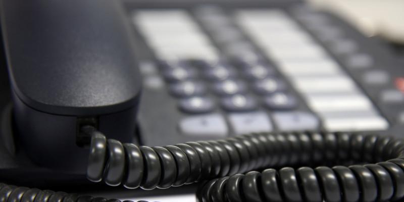 Nahaufnahme von einem schwarzen Telefonhörer mit Schnur