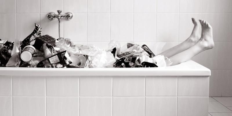 Scharzweiß Foto von einer Badewanne voller Plasikmüll aus der nur noch zwei Beine gucken