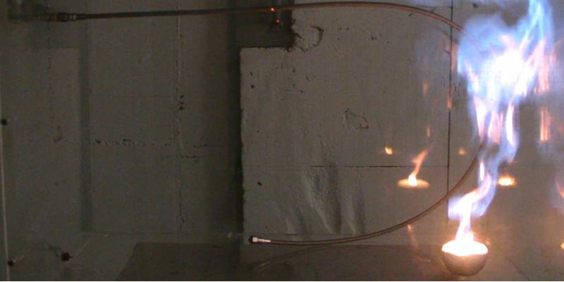 Ein Metallrohr ist U-förmig vor einer Wand gebogen. Auf der rechten Seite lodert eine große Flamme das ganze Rohr entlang.