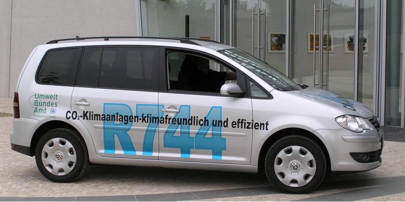"""Der silberne klimafreundliche VW Touran, auf dem in großer blauer Aufschrift steht: """"R744"""" und darüber kleiner und schwarz:""""CO2-Klimaanlagen - klimafreundlich und effizient""""."""