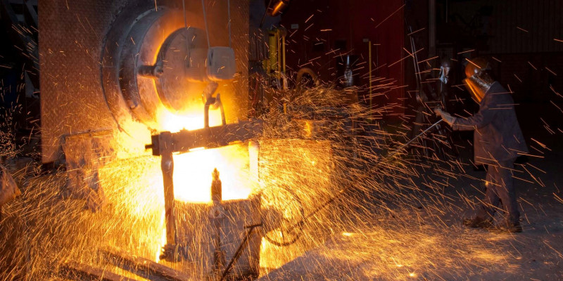 Eine Gießerei, bei der glühendes Metall verarbeitet wird und viele Funken sprühen.