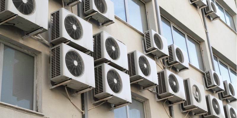 A lot of room air conditioners hangig on the face of a building