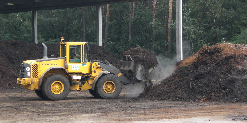 A yellow wheel loader implements composting in a composting plant.