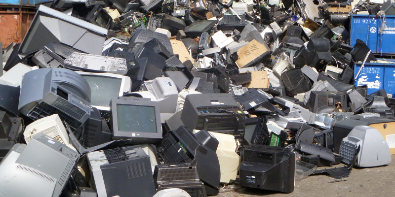 Old televisions and computer monitors on a pile.