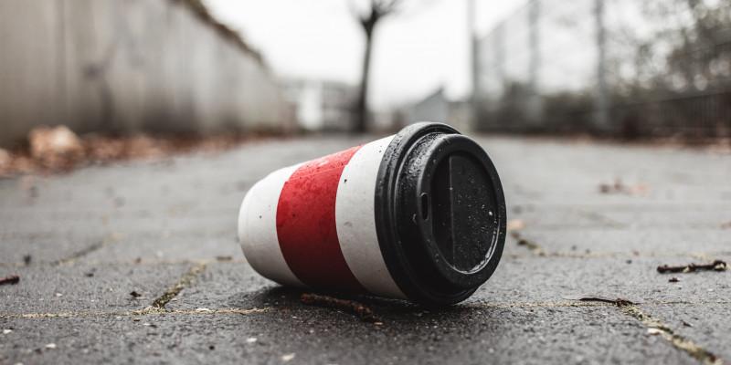 Ein Coffee-to-go-Becher liegt auf der Straße