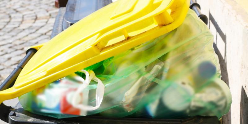 Eine gelbe Mülltonne mit einer Plastiktüte voller Verpackungsmüll.