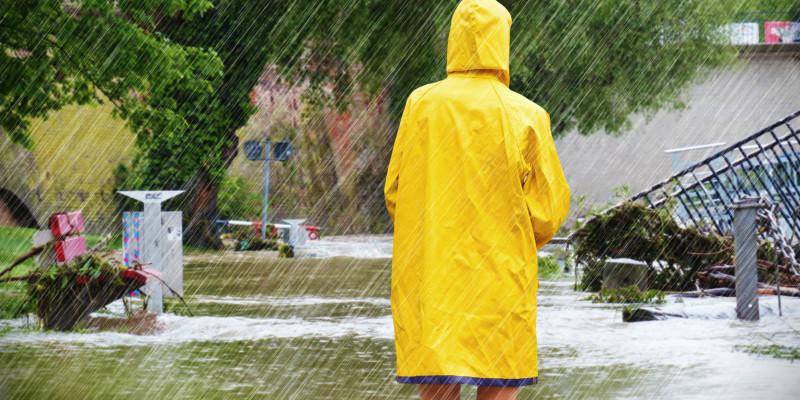Eine Frau mit Regenmantel steht im Regen vor einer überfluteten Landschaft.