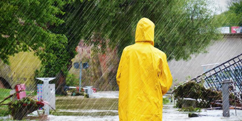 Eine Frau mit einer Regenjacke steht im Wasser.