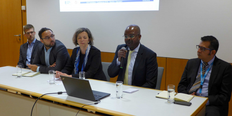 Ein Foto von der Konferenz: Fünf Personen sitzen hinter einem Konferenztisch.