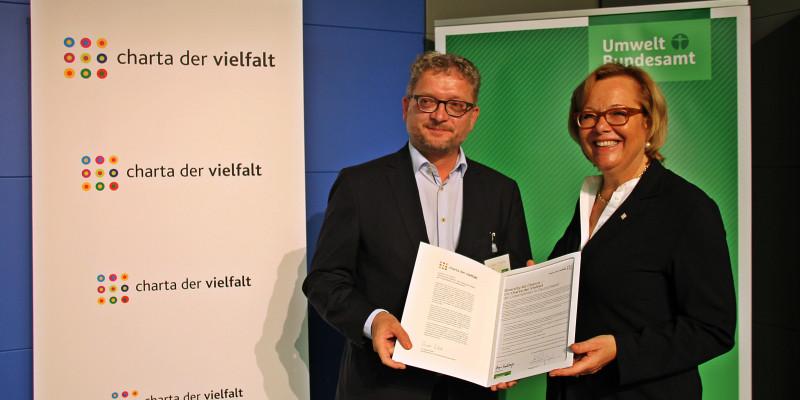 Zwei Personen mit der unterzeichneten Charta der Vielfalt