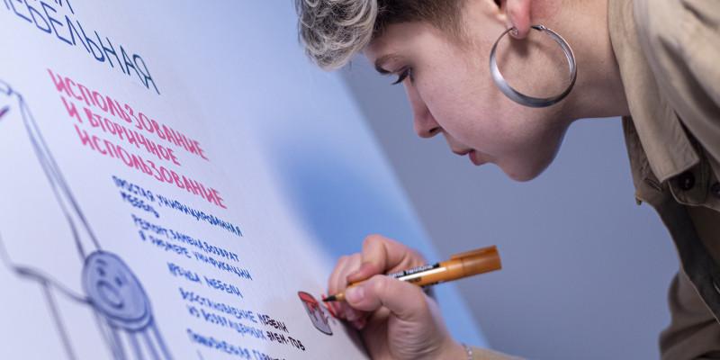 Eine Frau schreibt etwas auf einen Flipchart.