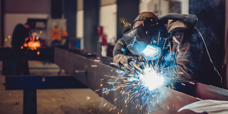 Ein Arbeiter schweißt einen Metallträger.