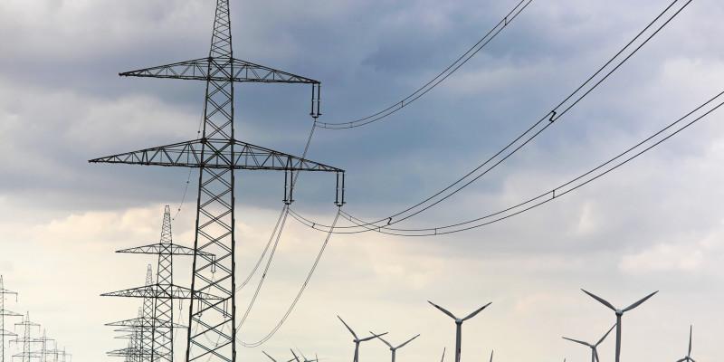 Ein Strommast mit Leitungen vor blauem Himmel.