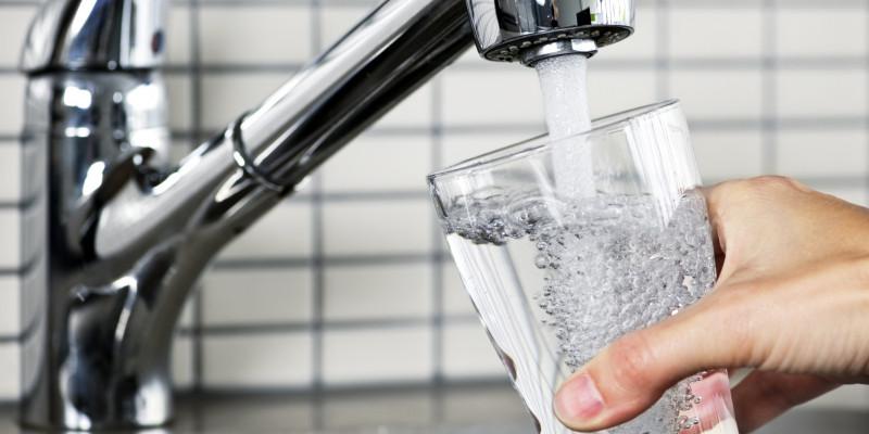 Ein Glas wird unter einem Wasserhahn gefüllt.