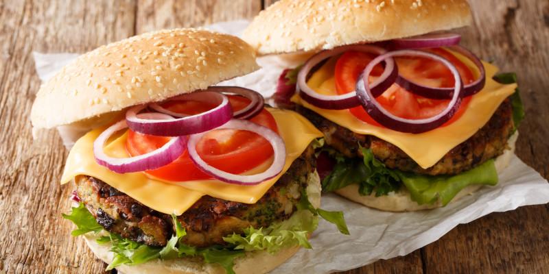 Zwei vegetarische Hamburger liegen auf einem Holzbrett