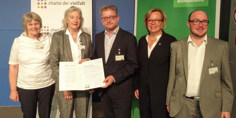 Fünf Personen mit der unterzeichneten Charta der Vielfalt.