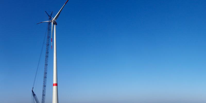 Eine Windkraftanlage in der Konstruktion vor blauem Himmel mit einem großen Kran.