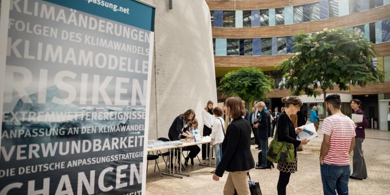 Sie sehen ein Bild vom Nationaler Dialog 2017 Gemeinsam sind wir klimaresilient – Wie Beteiligung in Städten und Regionen gelingt. Das Bild wurde im Umweltbundesamt in Dessau aufgenommen. Auf der rechten Seite sehen Sie ein Aufsteller zum Thema Klimarisiken und Anpassung. Auf der rechten Seite des Bildes sind Menschen auf dem Weg in den Hörsaal in Dessau.