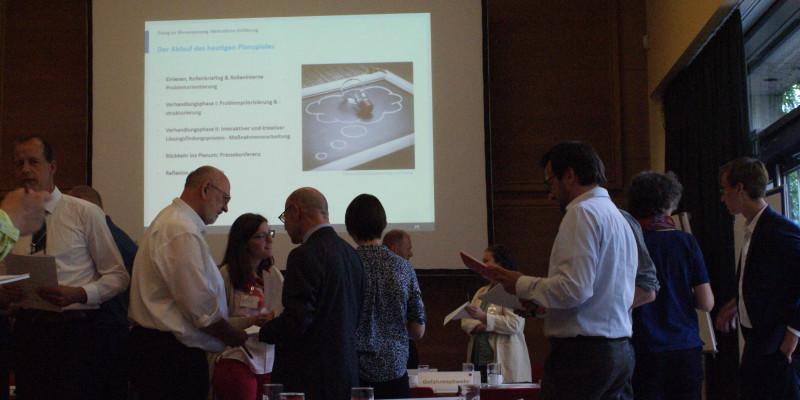 Ein Bild von dem Stakeholderdialog 2019: Katastrophenvorsorge bei Wasserengpässen kooperativ gestalten. Man sieht im Hintergund die PowerPoint Präsentation auf der das Planspiel erklärt ist, welches im Vodergrund abläuft. Personen stehen in kleineren Gruppen zusammen und diskutieren miteinander.
