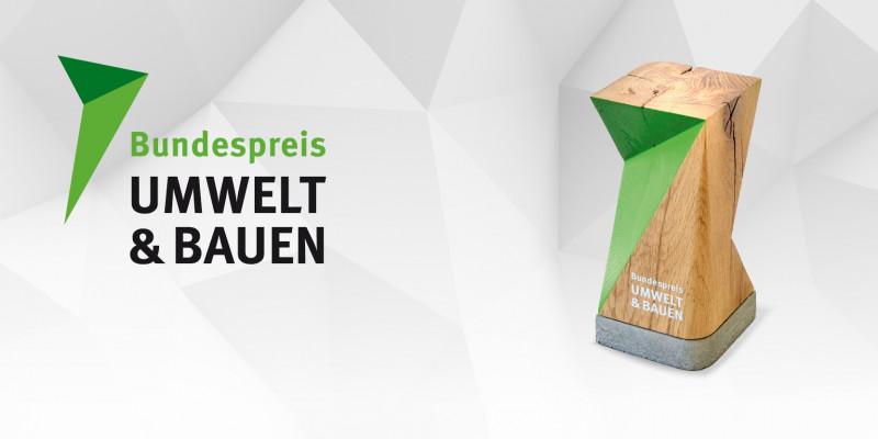 """Schriftzug """"Bundespreis Umwelt & Bauen"""" und Bild einer Trophäe aus Holz"""