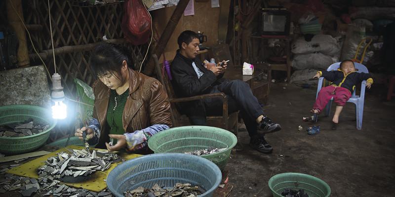 Frau sortiert Elektroschrott. Mann und Kind sitzen dahinter.
