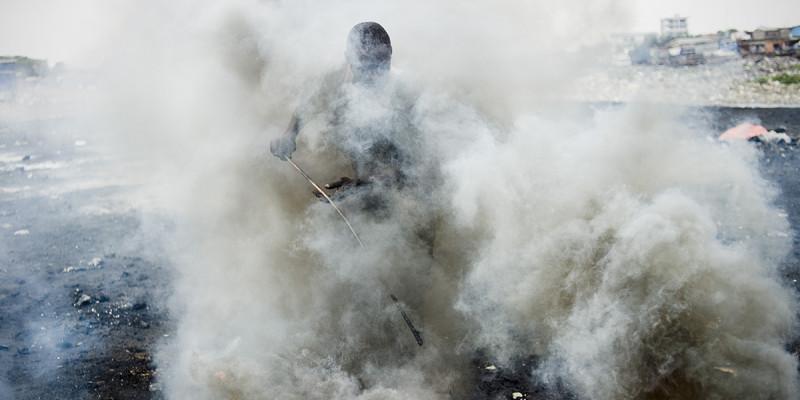 Mensch in Rauchschwaden bei der Verbrennung von Schrott.