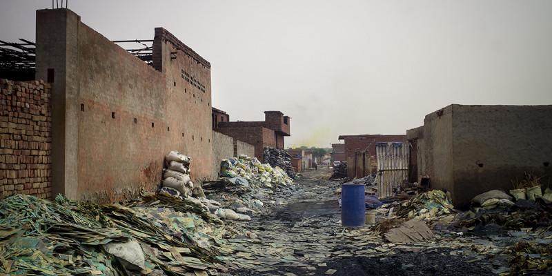 Straße voller Müll. Alte Gebäude links.