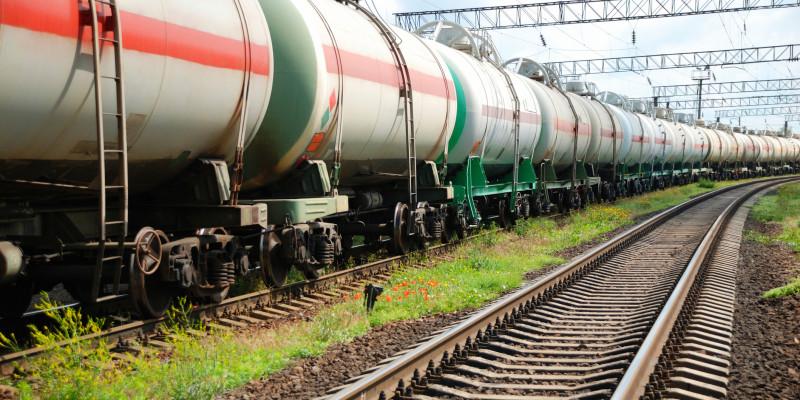Langer Güterzug auf einem Gleis. Daneben eine leere Schiene.