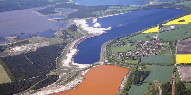 Luftbild einer Landschaft mit Tagebausee