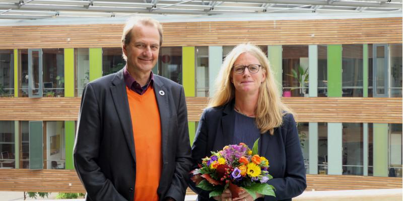 UBA Präsident Dirk Messner und Vizepräsidentin Lilian Busse mit einem Blumenstrauß