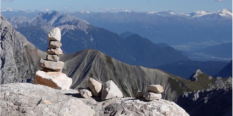 Aufgetürmte Steine im Vordergrund; Panoramablick über die Zugspitze im Hintergrund
