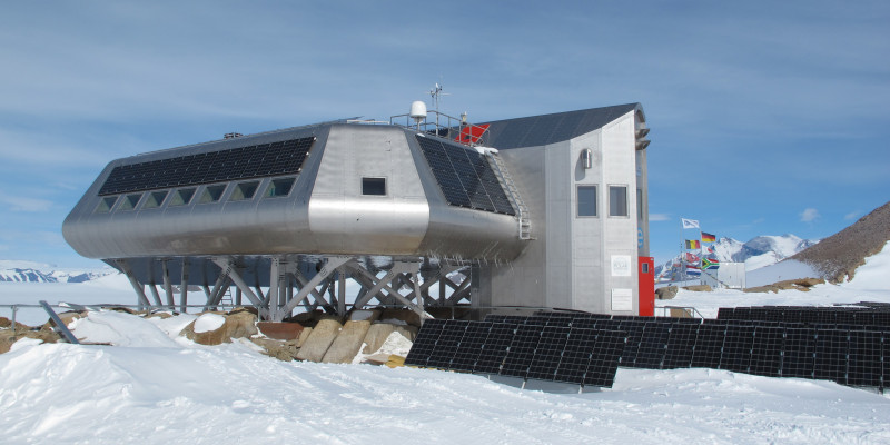 Im Schnee steht auf Stelzen ein Gebäude mit einer anthrazitfarbenen Verkleidung. Solarpanele sind auf der Station und daneben auf dem Boden angebracht. Im Hintergrund rechts befindet sich eine andere Station.